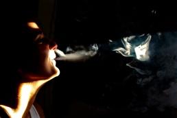 Young woman exhaling vapor
