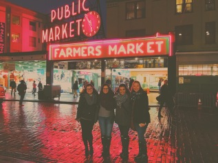 """Standing in front of a mostly-closed and deserted, but well lit Pikes Place Market with some convergence friends. Our iMessage chat name is """"Next Gen. Meg Ryan"""" and sleep or the smell of raw fish will not bring us down while in Seattle."""